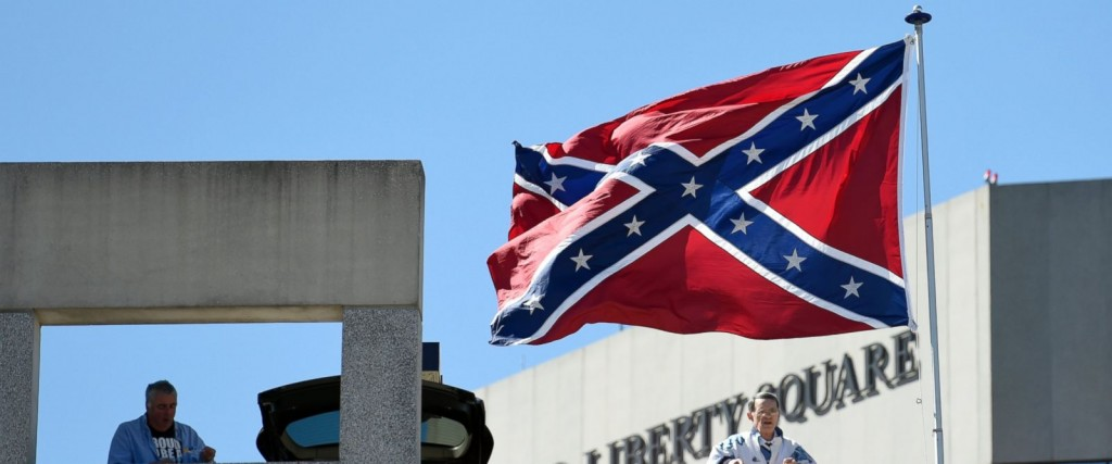 Basketball fans look out as a Confederate flag flies from a parking deck outside the arena before a second-round game of the NCAA men's college basketball tournament in Greenville, S.C., Sunday, March 19, 2017. A small group of protesters flew a large Confederate flag from the top of a parking garage next to the arena hosting two men's NCAA Tournament games. (AP Photo/Rainier Ehrhardt)