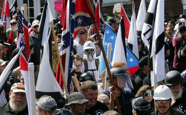 White nationalist demonstrators walk into the entrance of Lee Park surrounded by counter demonstrators in Charlottesville, Va., on Saturday, Aug. 12, 2017. (AP Photo/Steve Helber)