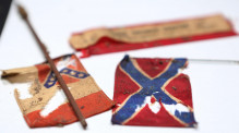 """Confederate flags were among the items found in the time capsule -- Orlando's historic preservation officer, Richard Forbes, opens the century-old time capsule that was found inside the base of the Confederate statue known as """"Johnny Reb,"""" on August 8, 2017. (Ricardo Ramirez Buxeda/ Orlando Sentinel)"""