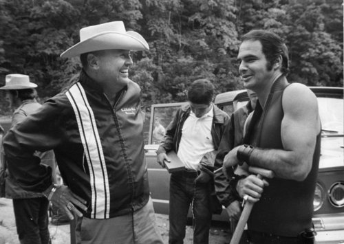 "James Dickey and Burt Reynolds on the set of Deliverance. According to a September 2011 issue of Atlanta magazine, Reynolds says, ""Dickey and I didn't see eye to eye, but I did love the book."" Before Dickey was banned from the set owing to his disruptive presence by director John Boorman, he earned the scorn of Reynolds and the other lead actors by calling them by their character's names and not their real names. Source: breathnaigh.org"
