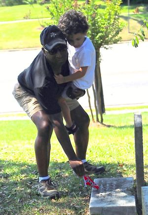 Myron Penn and his son removing Confederate flags from graves (Courtesy: Karen Penn)