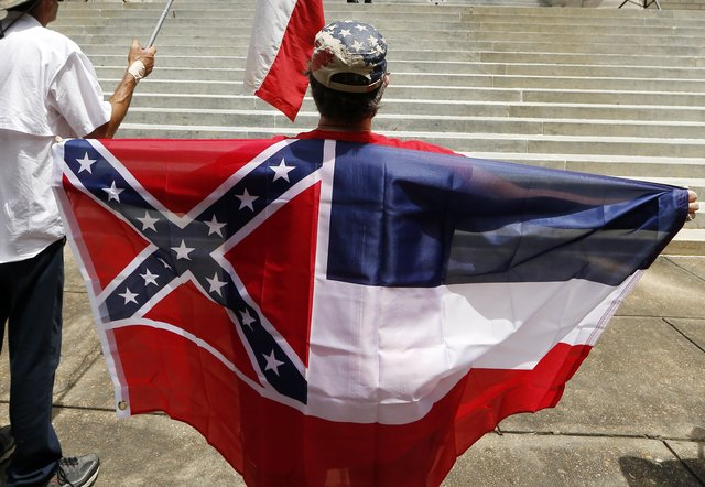 """In this July 6, 2015 photograph, a participant of a """"Save the Mississippi State Flag Rally"""" at the Capitol, holds a Mississippi flag as she listens to speakers in Jackson, Miss. Mississippi is the only state that includes the Confederate battle emblem in its state flag. The rebel X has been there since 1894. In a 2001 statewide election, people voted nearly 2-to-1 to keep the design. (AP Photo/Rogelio V. Solis)"""