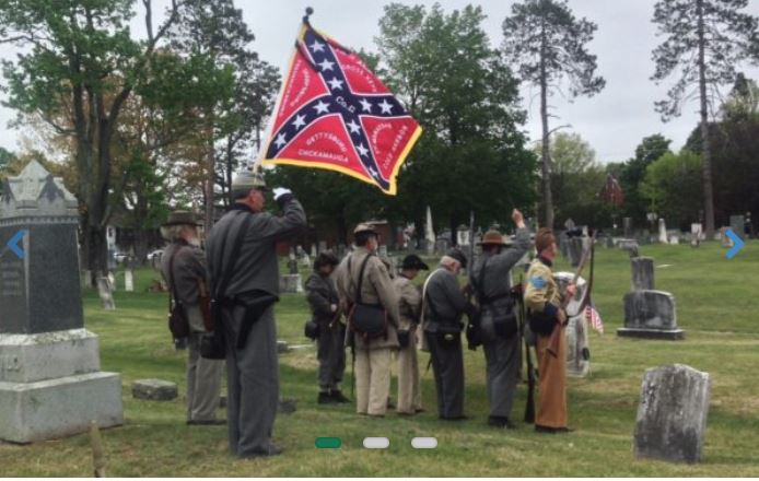 Members of the 15th Alabama fired blanks and saluted the graves of a Union and unknown Confederate soldier in the Gray village cemetery on Memorial Day, as they flew the Confederate battle flag.