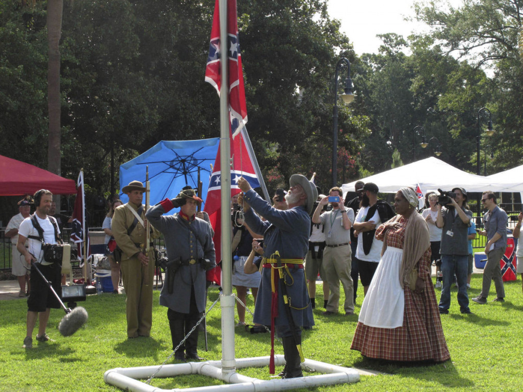 Arlene Barnum, right, watches as Braxton Spivey raises a Confederate flag on the grounds of the South Carolina Statehouse on July 10, 2017, in Columbia. The South Carolina Secessionist Party sponsored the event to commemorate the day the flag was removed from the front lawn of the state capitol. The Secessionist Party says it will raise the flag every July 10th so a year will never go by without the Confederate flag flying. (AP Photo/Jeffrey Collins)
